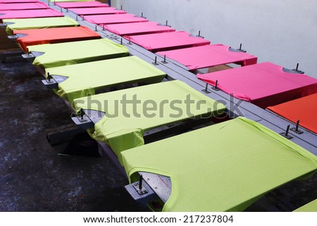 prepare colorful t-shirt on screen table - stock photo