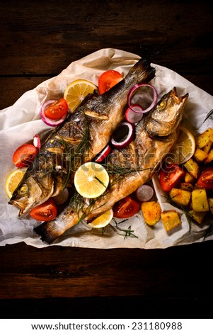 Prepared and grilled bass fish with potato and vegetables  - stock photo