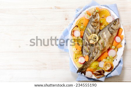 Prepared bass fish on white wooden background with blank space - stock photo