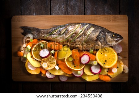 Prepared Bass fish with vegetables and fruit from above on wooden background  - stock photo
