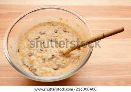 Prepared batter for banana loaf in a glass bowl with a wooden spoon