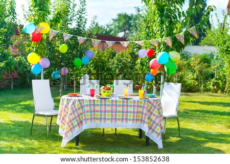 Prepared birthday table in summer green garden - stock photo