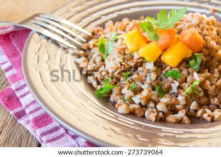 Prepared buckwheat with vegetables (tomatoes and parsley) on plate, close up, horizontal. Fresh vegetarian natural organic food. - stock photo