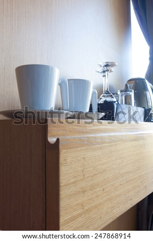 prepared cup and glass on wood shelf in luxury hotel room. - stock photo