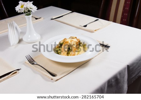 Prepared Dish Served at Place Setting with Fork and Knife on Restaurant Table Decorated with Vase of Flowers - stock photo