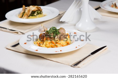 Prepared Dishes Served in White Bowls at Simple Individual Place Settings on Restaurant Table - stock photo