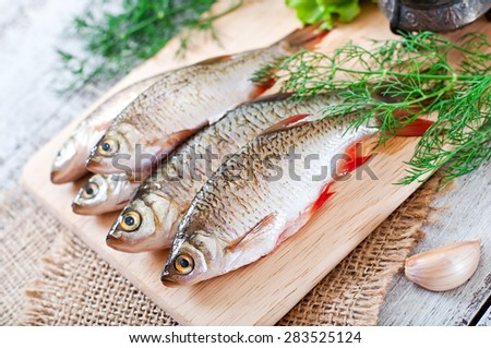 Prepared for frying fish roach on the wooden background. - stock photo