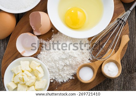prepared fresh baking ingredients on a wooden board, horizontal, top view, close-up - stock photo