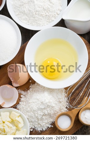 prepared fresh baking ingredients on a wooden board, top view, vertical - stock photo