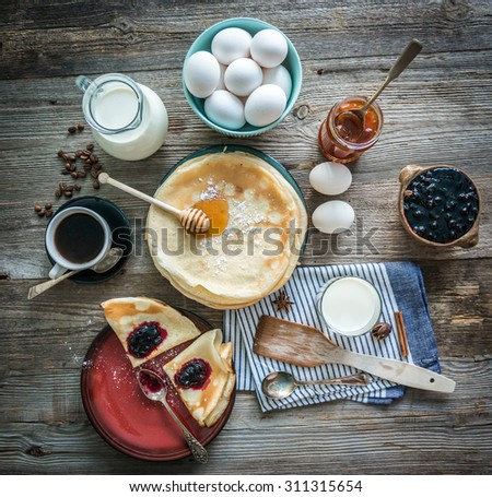 prepared pancakes and coffee among ingredients on wooden background - stock photo