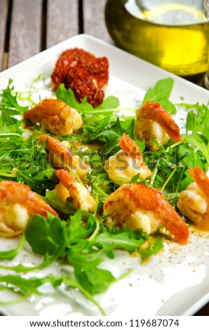Prepared plate with prawns and rocket, olive oil on background
