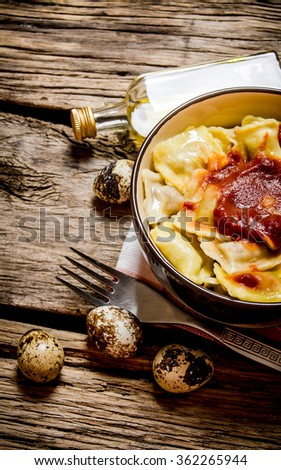 Prepared ravioli with tomato sauce in a Cup. On wooden background. - stock photo