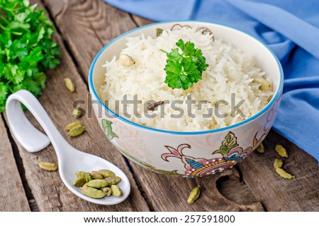 Prepared rice basmati  with clove and cardamom in oriental bowl on vintage background - stock photo