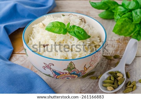 Prepared rice basmati  with clove and cardamom in oriental bowl on vintage background