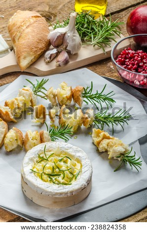 Prepareing for Baked Camembert with Garlic & Rosemary, with toast baked on rosemary stalk, fresh pomegranate, just DIP IN! - stock photo