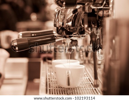 prepares espresso in his coffee shop; close-up  monotone