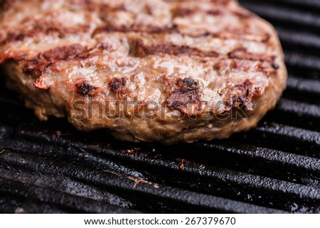 Preparing a batch of ground beef patties or frikadeller on grill or BBQ - stock photo