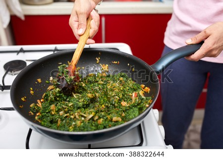 Preparing a delicious nettle porridge as side dish or vegetarian meal - stock photo