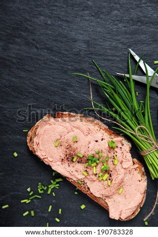 Preparing a delicious teewurst sandwich spread on a slice of rye bread and topped with chopped fresh chives on an old slate kitchen counter with copyspace - stock photo