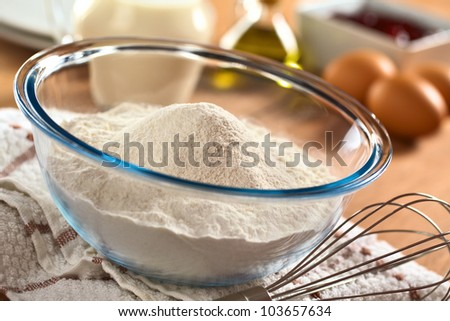 Preparing a dough/batter for crepes or pancakes with wheat flour in glass bowl, milk, eggs and oil in the back and a beater on the side (Selective Focus, Focus one third into the bowl) - stock photo