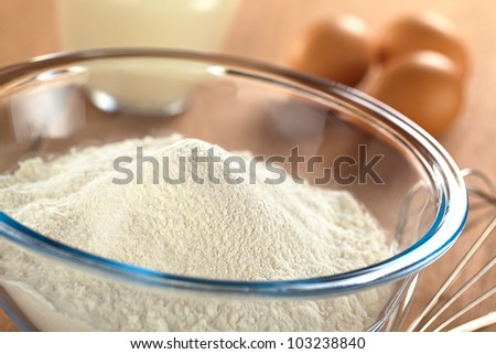 Preparing a dough for crepes or pancakes with wheat flour in glass bowl, milk and eggs in the back and a beater on the side (Selective Focus, Focus one third into the bowl) - stock photo