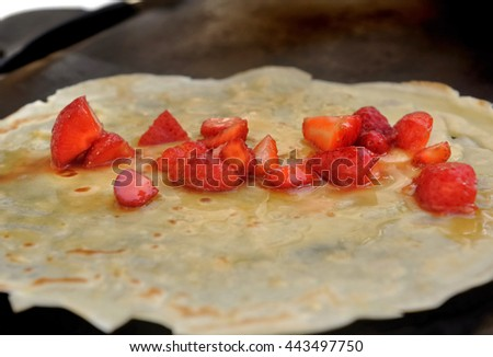 preparing a french pancake with strawberries and honey  - stock photo
