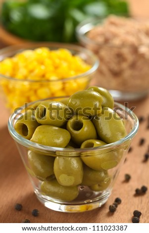 Preparing a fresh salad. Green olives with sweet corn, tuna and watercress (Selective Focus, Focus on the front of the olives on the top)