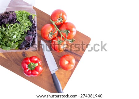 Preparing a healthy leafy green salad with farm fresh sweet bell pepper, tomatoes and assorted lettuce cultivars on a wooden chopping board with a knife, view from above on white with copy space - stock photo