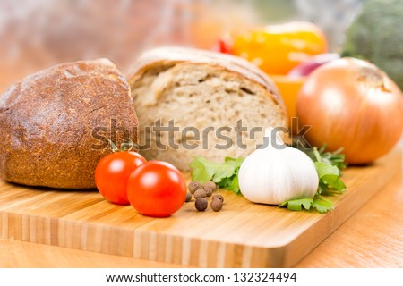 Preparing a meal with fresh whole garlic, tomato and parsley on a chopping board on a kitchen table with a loaf of bread and onion behind with shallow dof - stock photo