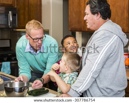 Preparing a meal with gay couple and kids in their home kitchen - stock photo