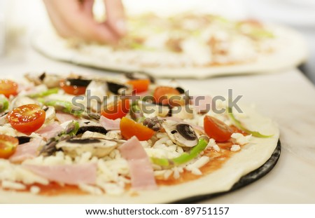 Preparing a pizza  putting various ingredients over the dough before cooking. - stock photo