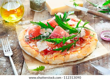 Preparing a tasty pizza in the kitchen using a crisp base topped with fresh herbs, ham, rucola, cheese and tomato - stock photo