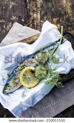 Preparing an baked fish in foil with sliced lemon, spices and assorted fresh herbs for cooking on an open barbecue fire or in the oven, high angle view in a rustic kitchen - stock photo
