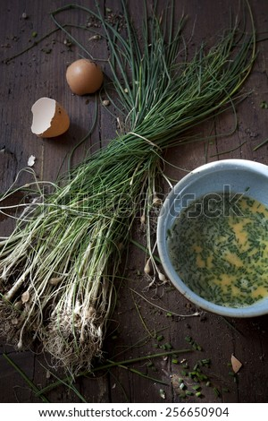 preparing an omelette with fresh beaten eggs and wild chives on bowl on rustic wooden table - stock photo