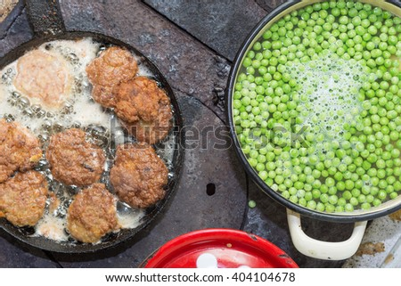 Preparing and cooking food on wood stove. - stock photo