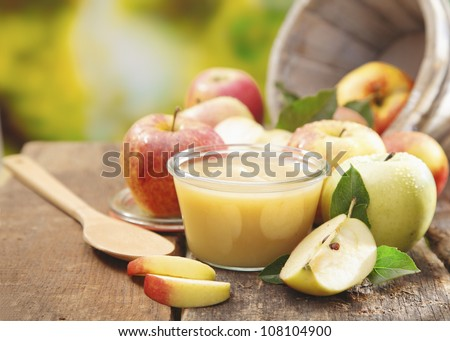 Preparing apple puree or sauce in a small glass jar with sliced apple pieces and a wooden spoon on an old wooden table outdoors - stock photo