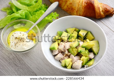Preparing chicken avocado salad with light yogurt dressing - stock photo