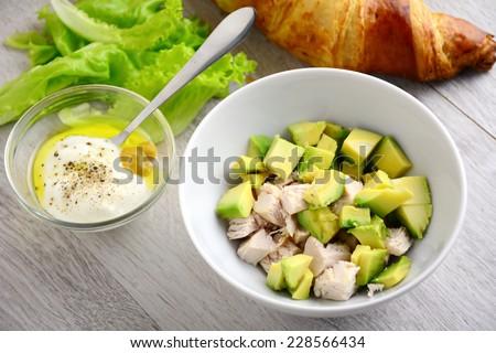 Preparing chicken avocado salad with light yogurt dressing on gray wooden table - stock photo