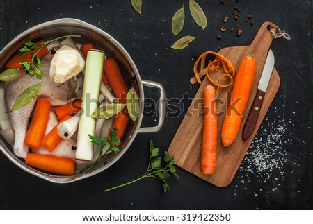 Preparing chicken stock with vegetables (bouillon) in a pot. Black chalkboard as background. Kitchen worktop scenery from above. - stock photo