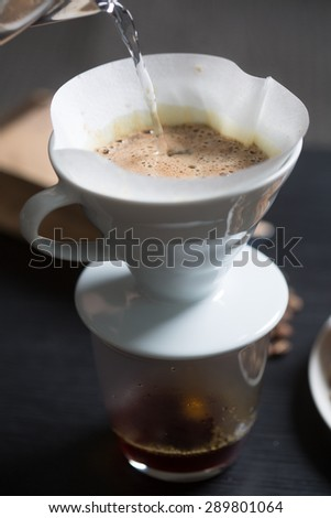 Preparing coffee in a manual filter pouring boiling water onto the freshly ground coffee beans, close up view of the water and frothy surface of the coffee - stock photo
