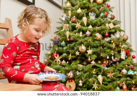 Preparing cookies for Santa Clause next to Christmas tree before going to bed. - stock photo