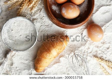 Preparing croissant on white flour background - stock photo