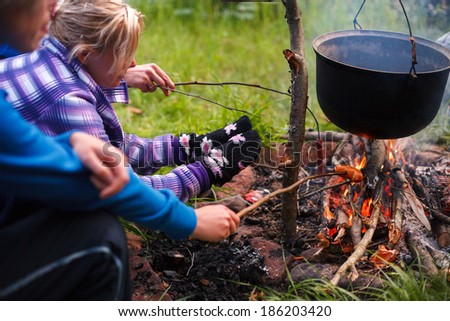Preparing food in wilderness, baking sausage on fireplace - stock photo