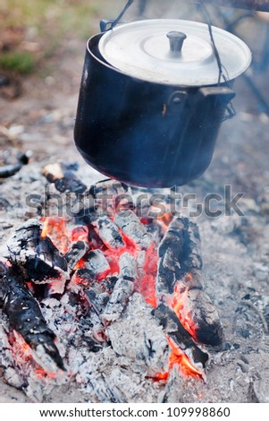 Preparing food on campfire - stock photo