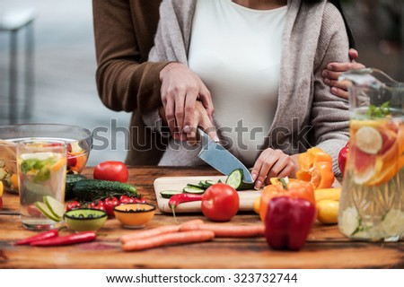 Preparing food together. Close-up of young couple cutting vegetables on the wooden table together - stock photo