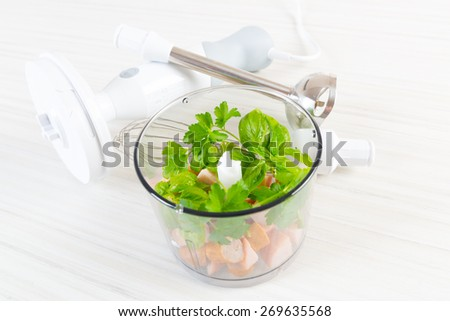 Preparing food with hand blender, green leaves and meat inside  - stock photo