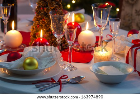 Preparing for Christmas Eve at beautifully decorated table - stock photo
