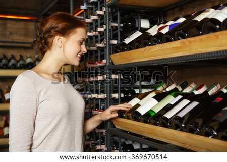 Preparing for dinner. Horizontal portrait of a beautiful young woman choosing bottle of wine in a wine cellar - stock photo