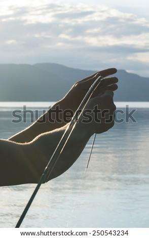 Preparing for fishing. Man put a hook. Bulgaria - stock photo