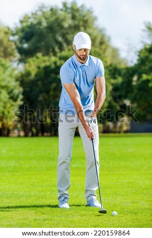 Preparing for shot. Full length of young man in sports clothing playing golf while standing on green - stock photo